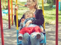 Mother swings on a swing with her small daughter royalty free stock image