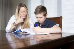 Mother at a table  home helping her small son with his homework. A mother at a table at home helping her small son with his homework from school Stock Images
