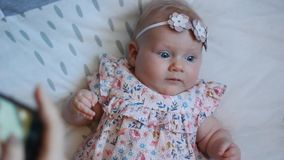 Three Months Old Baby Girl With Blue Eyes. Newborn Child, Little Adorable Peaceful and Attentive Girl Looking Surprised Smiling at. Mother take a photo of the stock video