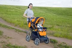 Mother takes baby in a stroller Stock Photos