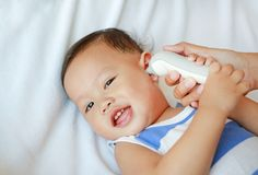 Mother takes temperature for baby boy with ear thermometer on bed at home royalty free stock photo