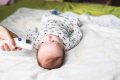 Mother taking baby temperature stock images