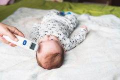 Mother taking baby temperature stock photos