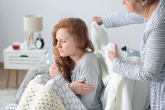 Mother taking care of daughter. Mother taking care of her sick daughter sitting on bed with fever and headache Stock Photos