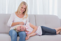 Mother taking care of her daughter. In the living room Stock Images