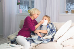 Mother taking care of her sick child, wiping her face with handkerchief. Caring mom staying with ill daughter Royalty Free Stock Image