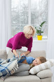 Mother taking care of her sick kid at home. Mom carefully covering her daughter with plaid Royalty Free Stock Image