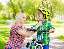 Mother taking care of her son, wearing his bicycle helmet Royalty Free Stock Photo