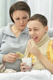 Mother taking care of son. Mother taking care of ill son at home Stock Photography