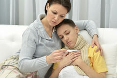 Mother taking care of son. Mother taking care of ill son at home Royalty Free Stock Images