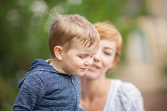 Mother taking care about young little boy in the park Royalty Free Stock Photos