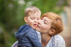 Mother taking care about young little boy in the park Royalty Free Stock Images