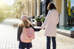Mother taking child to school. Holding hands, background - autumn city. Woman and girl with backpack behind the back stock photos