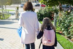 Mother taking child to school. Holding hands, background - autumn city. Woman and girl with backpack behind the back royalty free stock photography