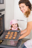 Mother taking cookies out of the oven with daughter Royalty Free Stock Photos