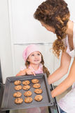 Mother taking cookies out of the oven with daughter pointing at one Royalty Free Stock Image