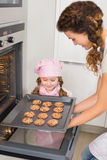 Mother taking cookies out of the oven with little girl watching Stock Image
