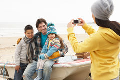 Mother Taking Family Photograph On Winter Beach. Smiling Royalty Free Stock Photos