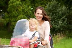 Mother taking her daughter on bicycle ride in the park Royalty Free Stock Photography