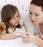 Mother taking her daughter's temperatu. Portrait of mother taking her daughter's temperature in bed Stock Images