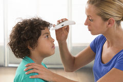 Mother taking little boy's temperature Stock Image