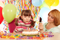 Mother taking picture while daughter blowing the candles Royalty Free Stock Image