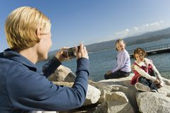 Mother taking picture of daughters at the lake Stock Images