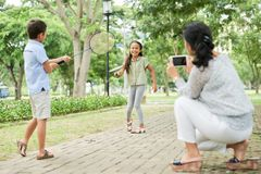 Mother taking picture of kids playing badminton stock photos