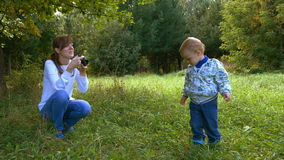Mother taking a pictures using retro film camera of her baby boy in a summer park stock video