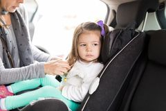 Mother Taking Precautions For Girl In Car. Sad girl looking away while mother adjusting car seat for her stock photos