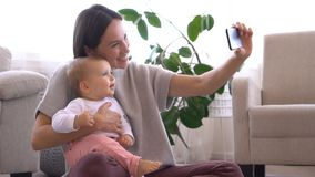 Mother taking selfie with baby girl using mobile phone stock video
