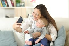 Mother taking a selfie with her baby son. Sitting on a couch in the living room at home Stock Photography