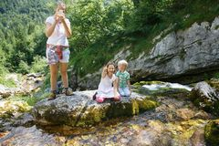 Mother taking a snapshot on a family trip with kids by a mountain stream. Outdoor lifestyle, positive parenting, childhood experience concept stock images