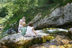 Mother taking a snapshot of kids on a family trip by a mountain stream. Outdoor lifestyle, positive parenting, childhood experience concept royalty free stock photos