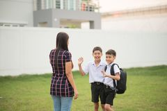 Mother taking sons to school together, hand wave say goodbye stock photography