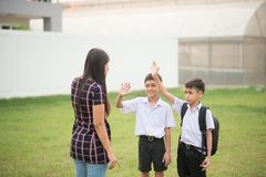 Mother taking sons to school together, hand wave say goodbye stock image