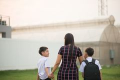 Mother taking sons to school together, hand wave say goodbye stock photos