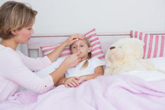 Mother taking the temperature of sick daughter. At home in the bedroom Royalty Free Stock Photos