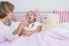 Mother taking the temperature of sick daughter. At home in the bedroom Stock Image