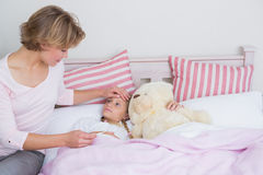 Mother taking the temperature of sick daughter. At home in the bedroom Stock Images