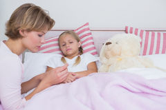 Mother taking the temperature of sick daughter. At home in the bedroom Royalty Free Stock Image