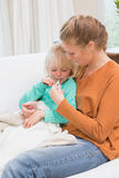 Mother taking the temperature of sick daughter. At home in the living room Stock Photos