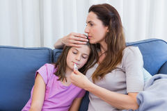 Mother taking temperature of sick daughter. At home in the living room Stock Photography