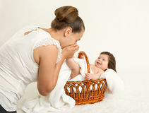 Mother talk with baby in basket on white towel, family concept, yellow toned royalty free stock photography