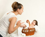 Mother talk with baby in basket on white towel, family concept, yellow toned Royalty Free Stock Photos