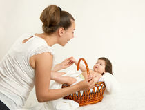 Mother talk with baby in basket on white towel, family concept, yellow toned Stock Photos