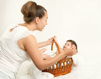 Mother talk with baby in basket on white towel, family concept, yellow toned Royalty Free Stock Images