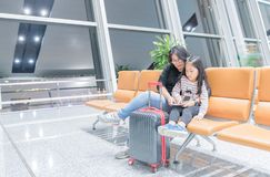 Mother talk with her daugther in airport. Young mother talk with her daugther about trip on chair in airport, travel concept Royalty Free Stock Photography
