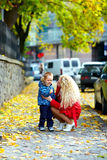 Mother talking with crying baby on city street Stock Image
