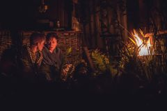 Mother talking with her mature teenager son around the campfire at night in countryside Stock Images